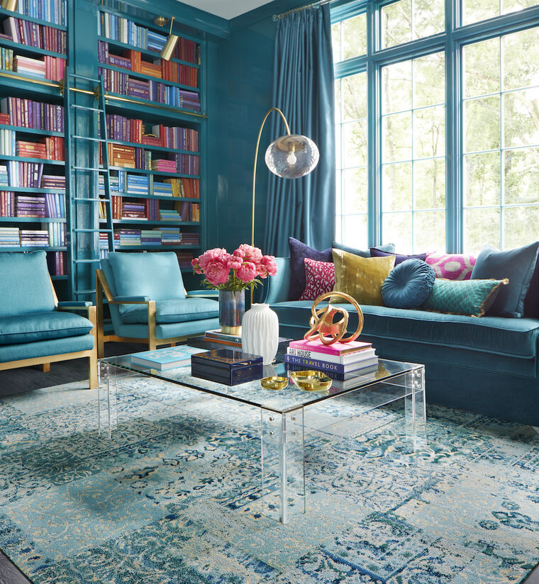 FLOR Reoriented living room rug in Teal with teal and wood couch and chairs and glass table.