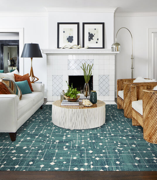 FLOR Hollin Hills area rug in Teal, a white couch, wicker chairs, round white coffee table, and a white tile fireplace.