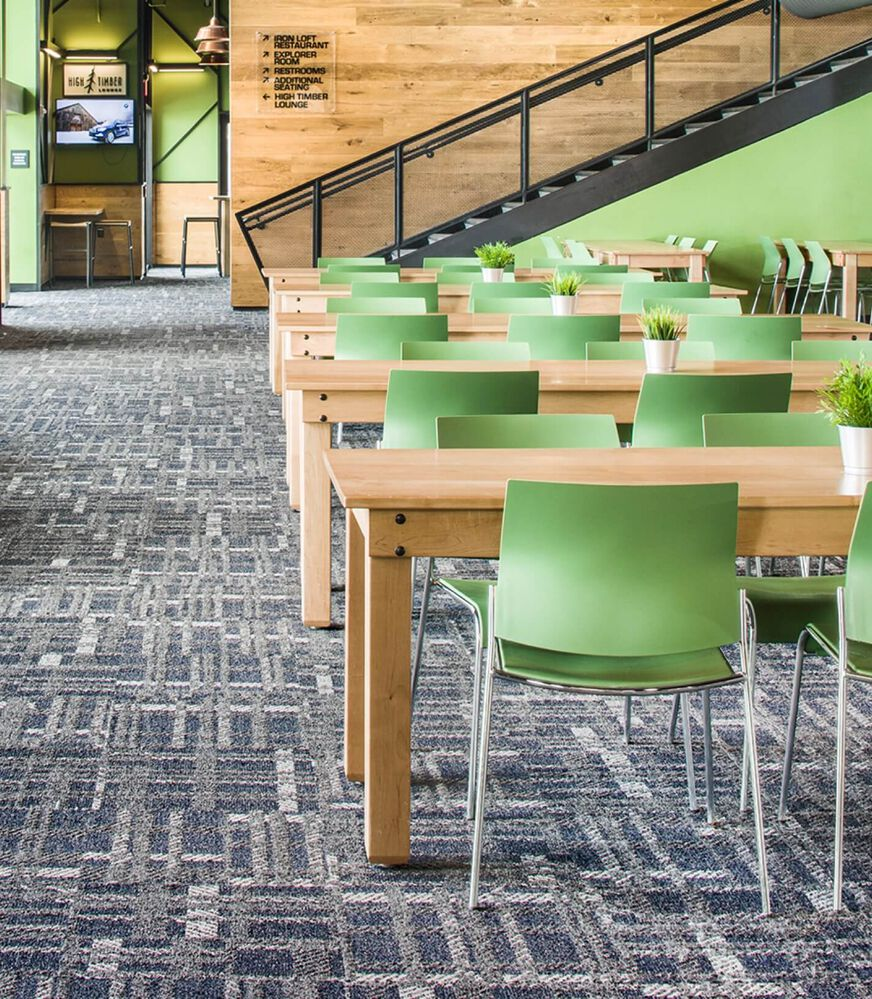 Green office chairs, wood tables, a green and black staircase, and gray plaid FLOR commercial carpet tiles.