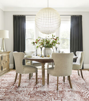 FLOR La Chinoise area rug in Spice in a white dining room, cream chairs, wood dining table, and black curtains.