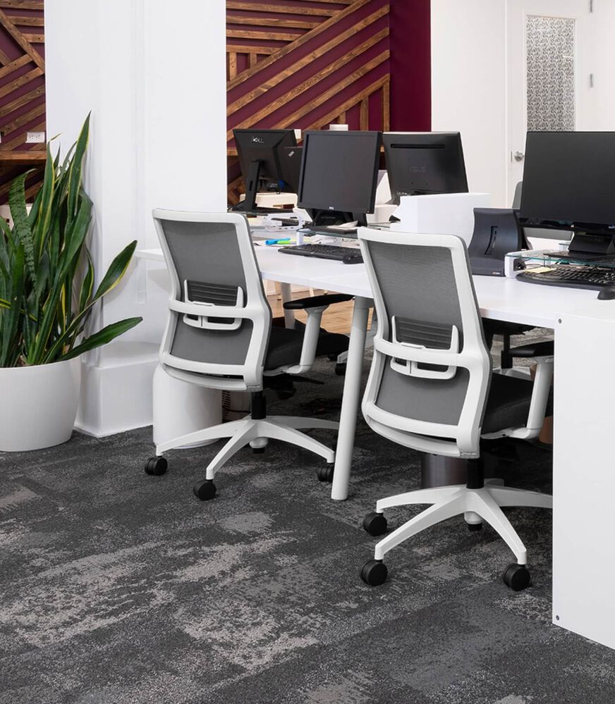 Close view of white office chairs, a white desk, a white column, computer screens, and gray FLOR commercial carpet tiles.