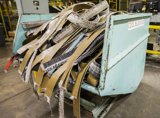FLOR carpet tiles being recycled in a light blue machine.