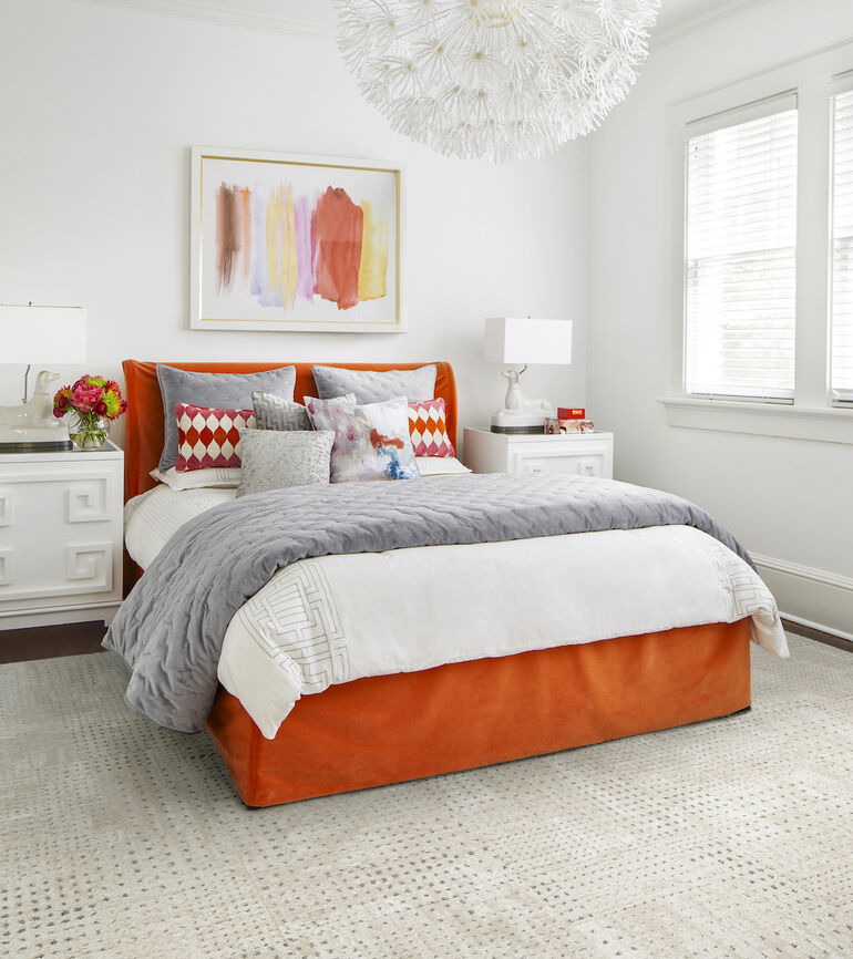 FLOR On The Dot bedroom rug in Bone / Silver with an orange, gray, and white bed.