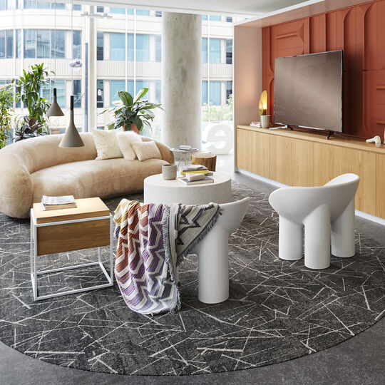FLOR Chasing Pavement area rug in Flint/Gold, a curved cream couch, white table, white chairs, and wood and metal table.