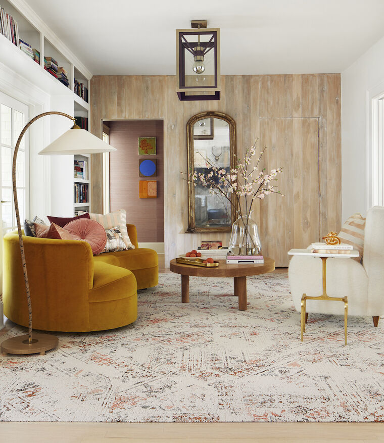FLOR Heart and Sole area rug in Coral, a yellow couch, white chair, wood table, and bronze floor lamp.