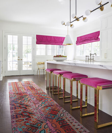 FLOR Over The Moon runner rug in Persimmon in a white, pink, and gold kitchen.