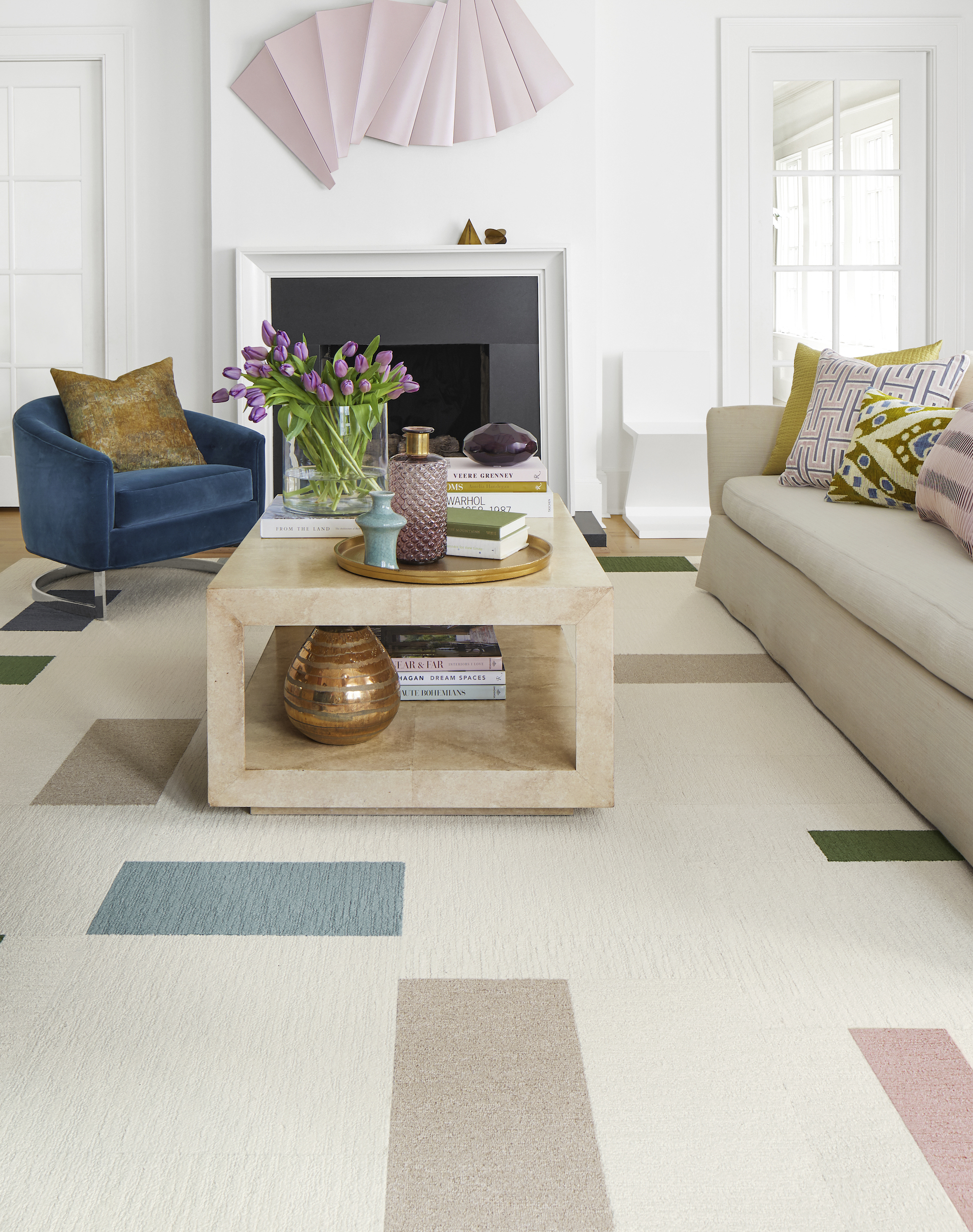 FLOR Made You Look area rug in Bone, Beige, Flannel Blue, Blush, Forest, and Slate, a cream couch, blue chair, and square coffee table.