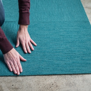 Hand of a person installing teal FLOR carpet tiles on a concrete floor.