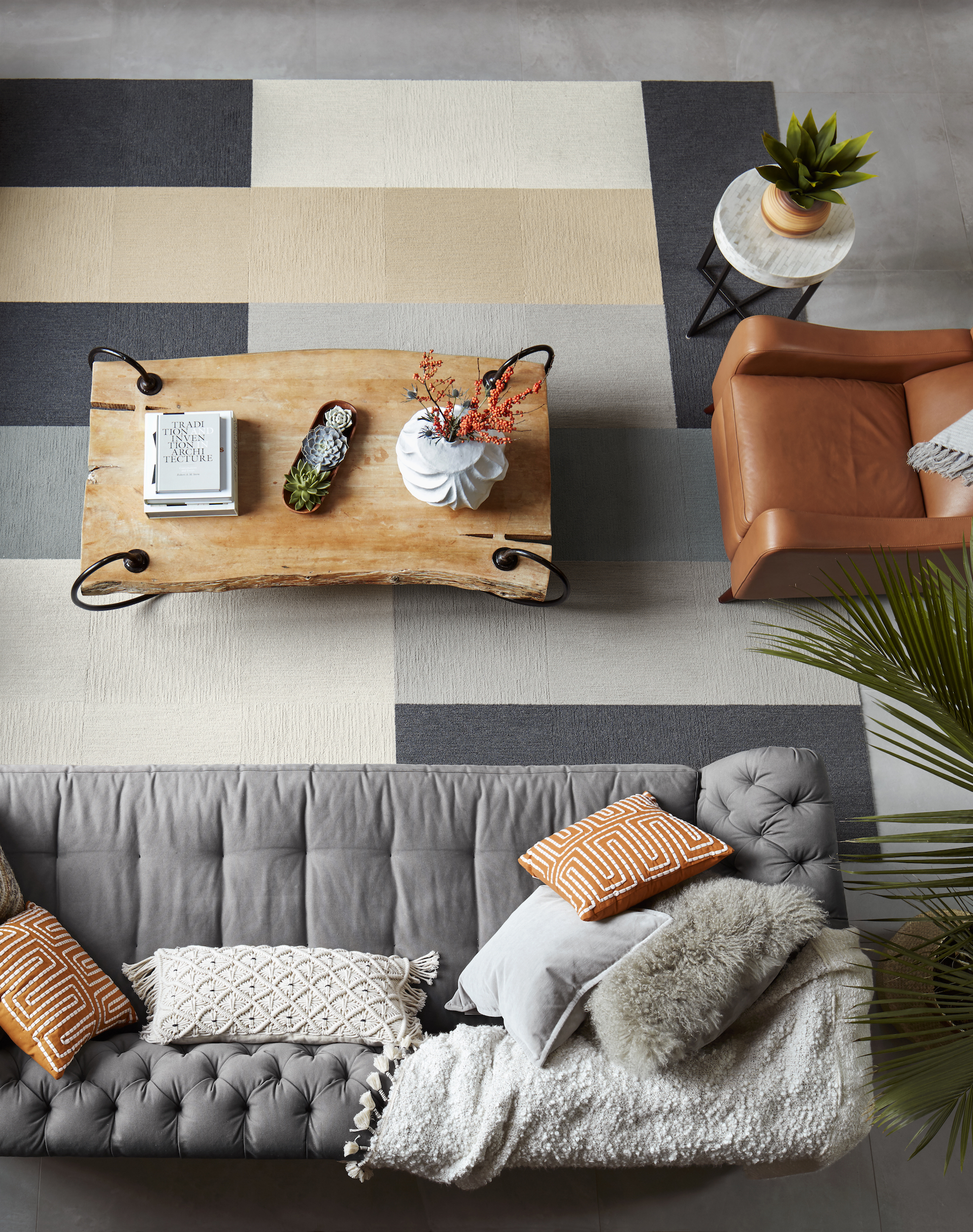 Overhead view of a gray couch, brown chair, metal table, metal side table, and FLOR Made You Look area rug in Bone, Granite, Flannel Blue, Eggnog, and Chalk.