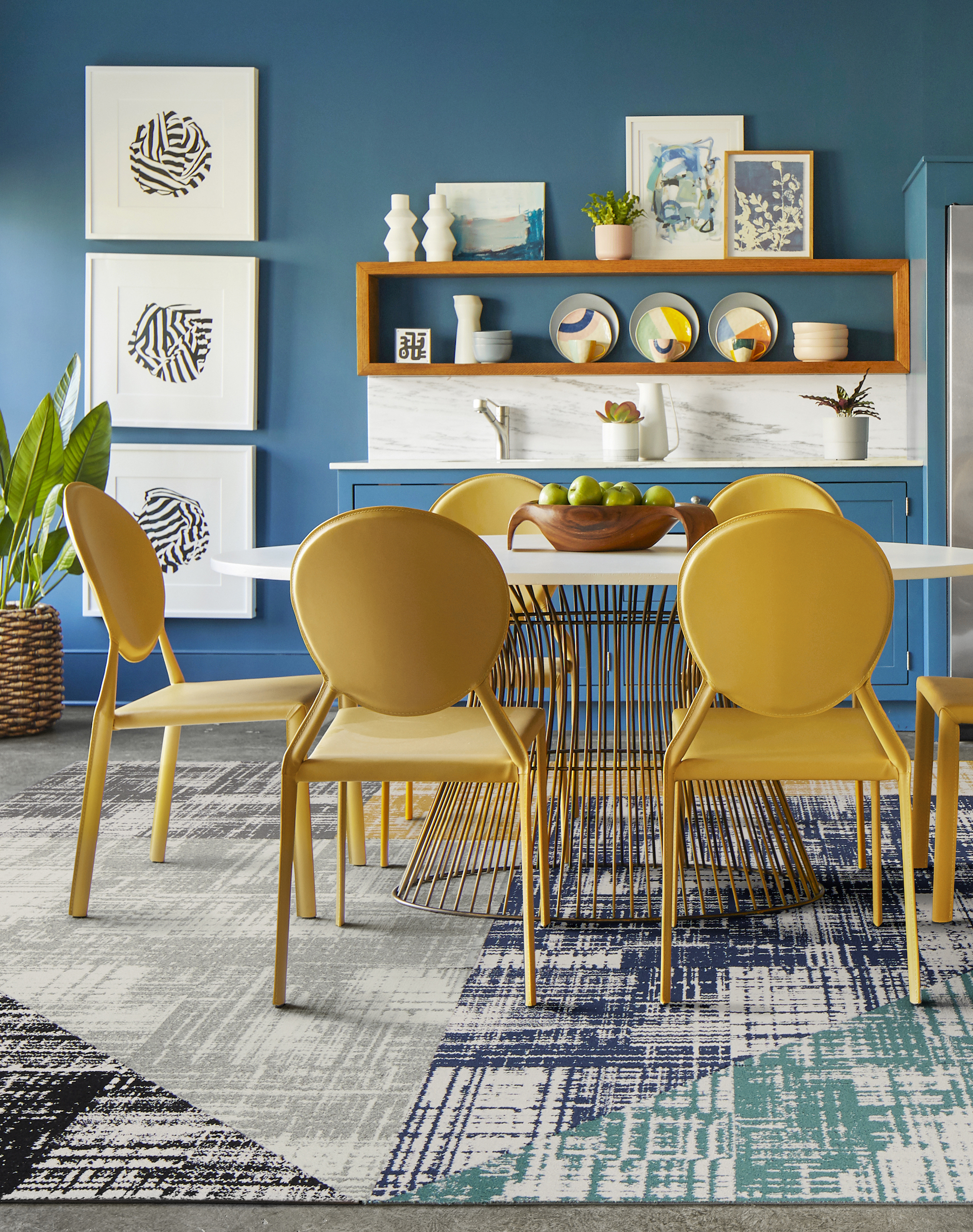 FLOR Dappled Daylight area rug in Black, Pigeon, Titanium, Marigold, Cobalt, and Teal, yellow chairs, and a metal dining table.