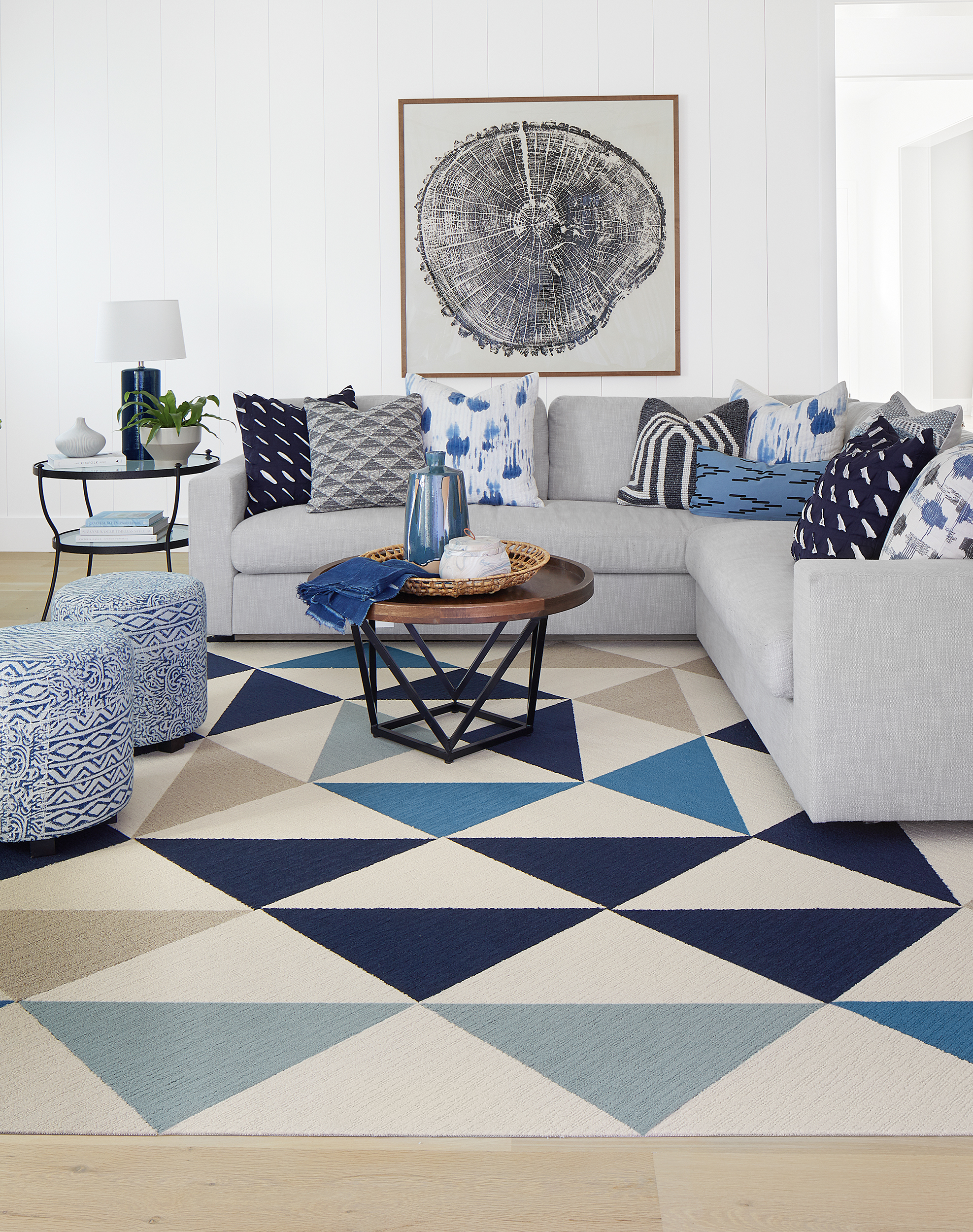FLOR Made You Look area rug in Beige, Bone, Indigo, Tidal, and Flannel Blue, a white couch, blue printed ottomans, and metal tables.