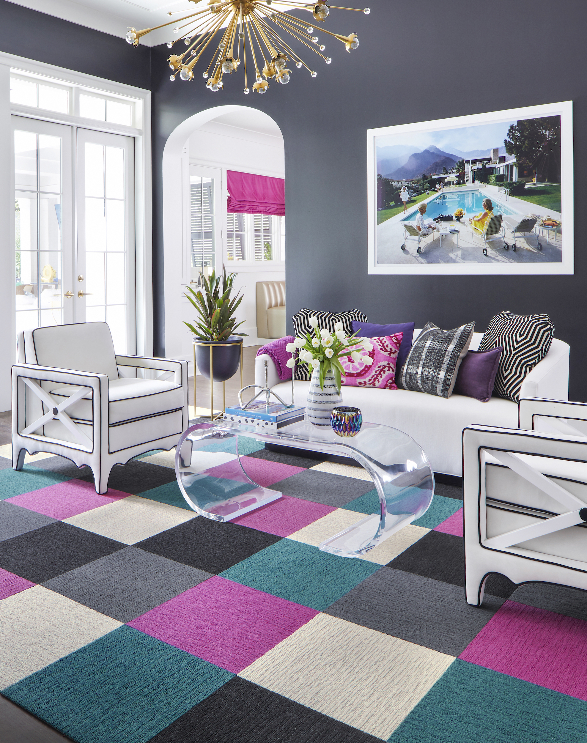 FLOR Made You Look area rug in Bone, Black, Magenta, Slate, and Turquoise, a white couch, purple, pink, and black pillows, white chairs, and a clear table.