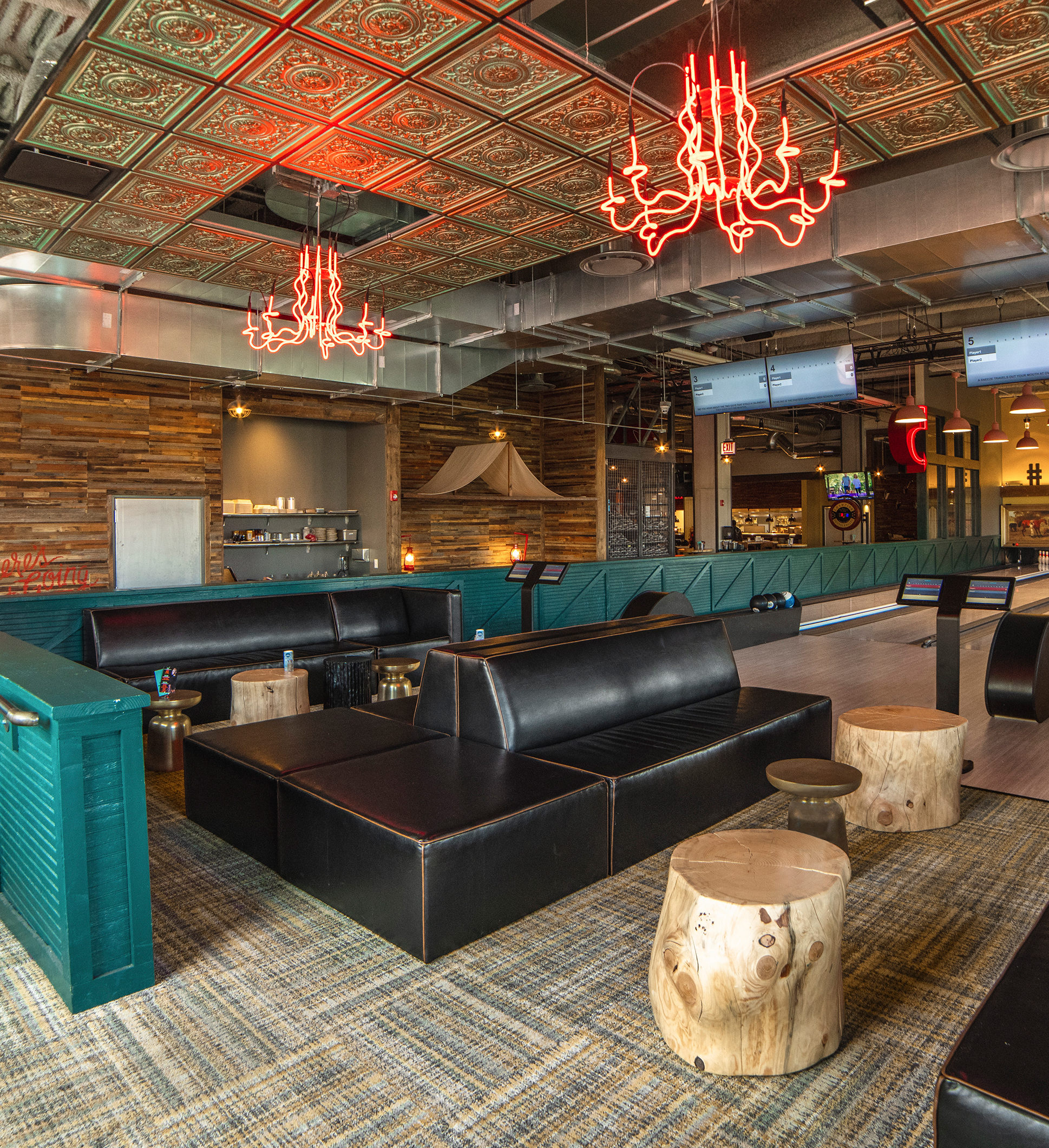 FLOR tan plaid commercial carpet tiles, black booths, teal half walls, and orange neon chandeliers.