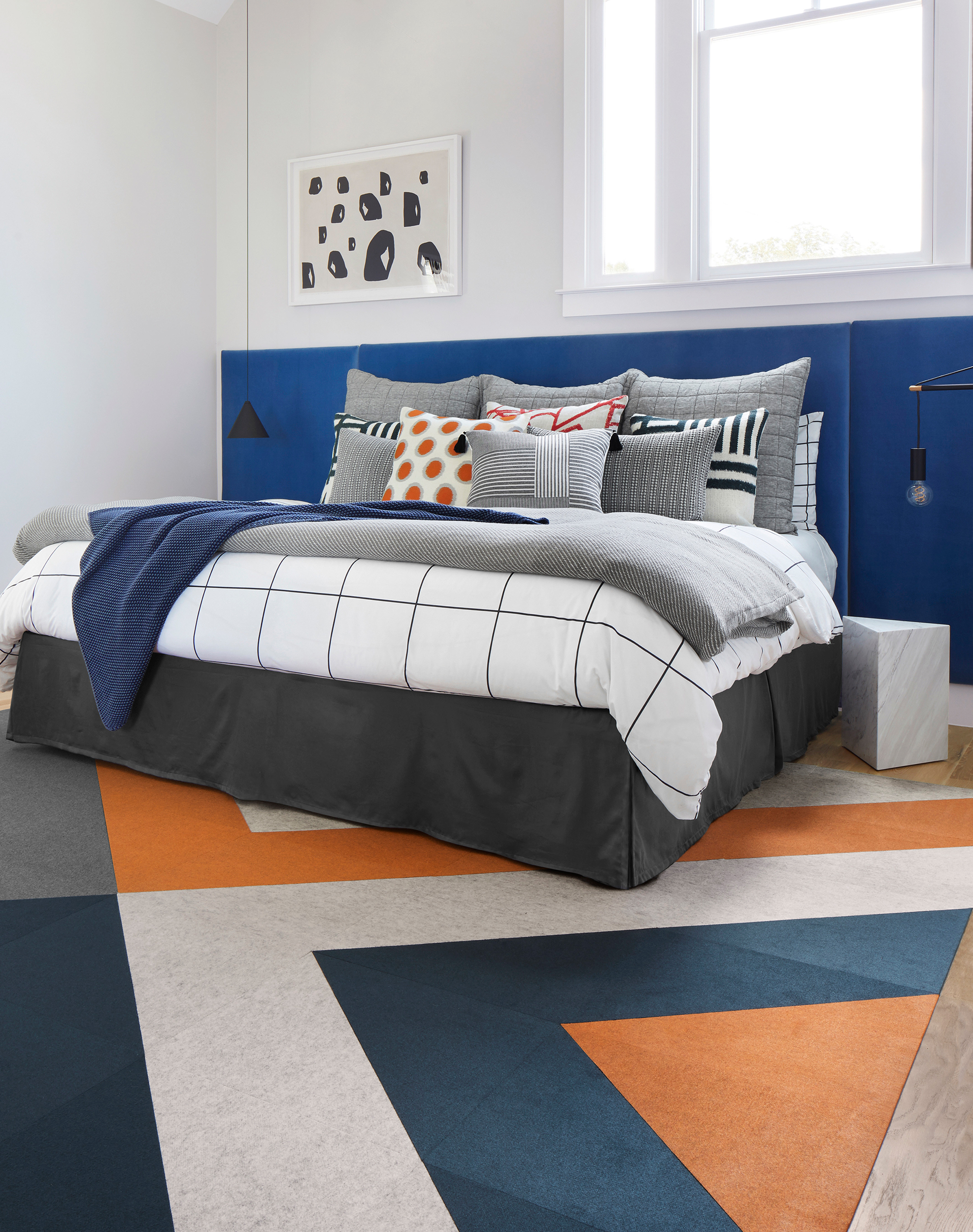 FLOR Fedora area rug in Oatmeal, Clementine, Flannel, and Lagoon, bed with blue, black, white, and gray bedding, and a marble side table.