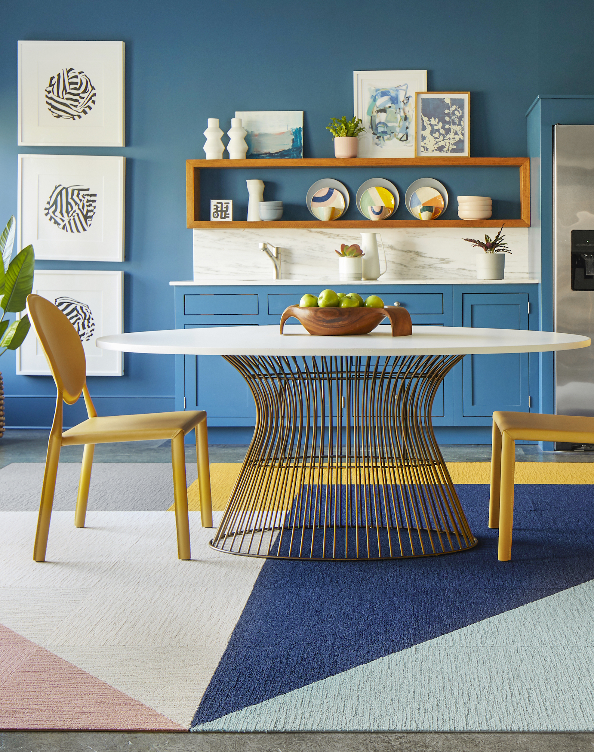 FLOR Made You Look area rug in Blush, Bone, Grey, Marigold, Indigo, and Seafoam, yellow chairs, and a metal dining table.