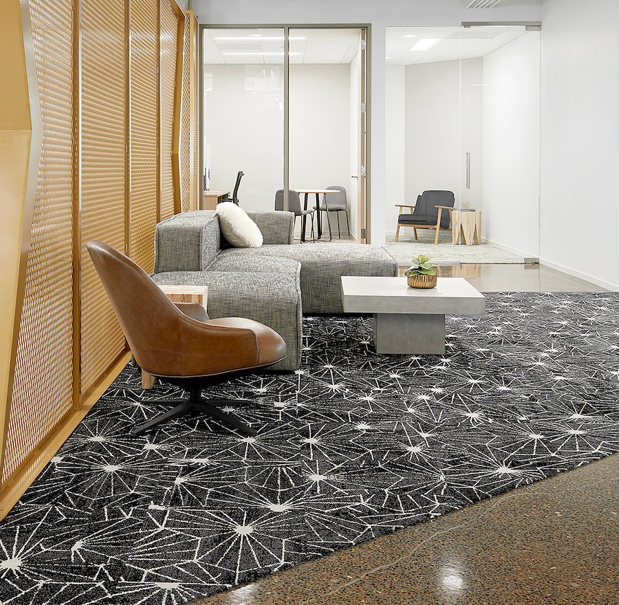 FLOR black and white starburst pattern commercial carpet tiles, gray sectional couch, brown leather chair, and white table.