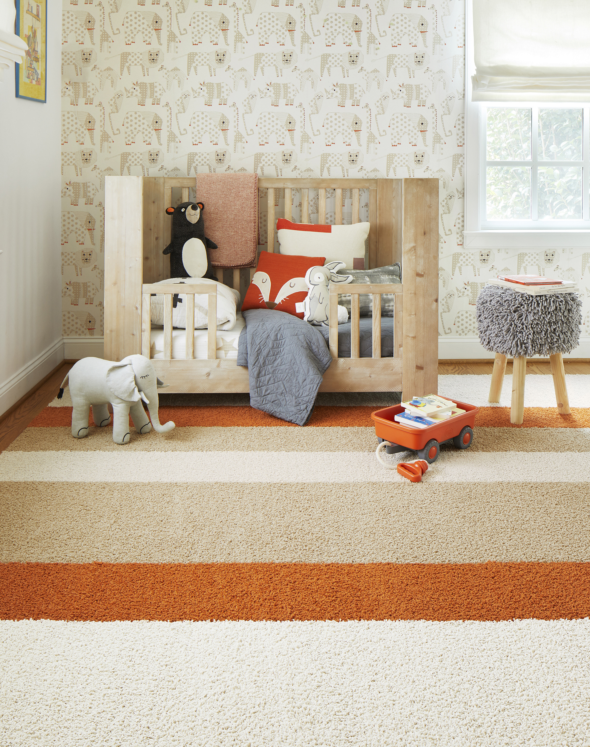FLOR In the Deep striped nursery rug in Bone, Clementine, and Eggnog, a light wooden toddler bed, and a shaggy gray stool.