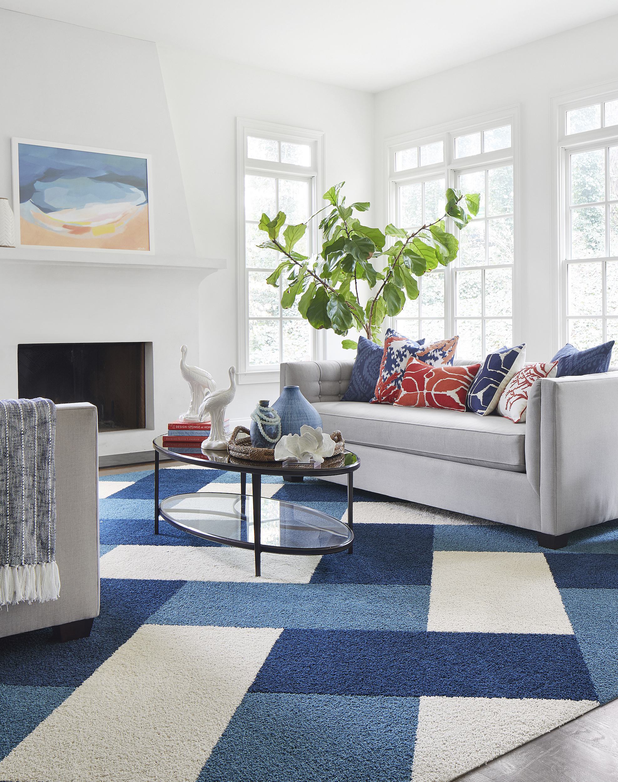 FLOR In the Deep area rug in Bone, Cobalt, and Tidal, a gray couch, blue and orange pillows, and an oval coffee table.