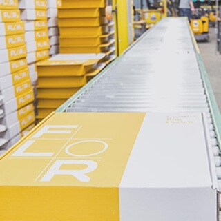 Yellow FLOR carpet tile box on a roller conveyor table in front of stacks of yellow FLOR boxes.